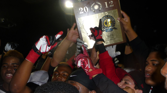 Corona Centennial players swarm around the CIFSS Inland Division championship plaque, hoping to touch it after their team defeated nationally ranked Vista Murrieta 30-28 in game played Nov. 30 at Vista Murrieta.