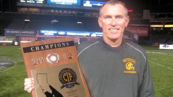 Head coach Dave White from Edison of Huntington Beach shows off hardware won by his team Friday night at Anaheim Stadium. The Chargers topped Villa Park for the CIFSS Southwest Division title.