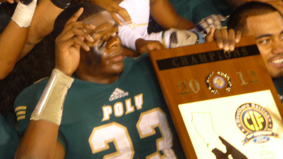 Long Beach Poly running back Gerard Wicks holds CIFSS Pac-Five title plaque during photo shoot.